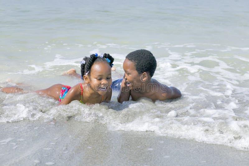 Afrikaanse Amerikaanse kinderen die bij het strand spelen royalty-vrije stock foto
