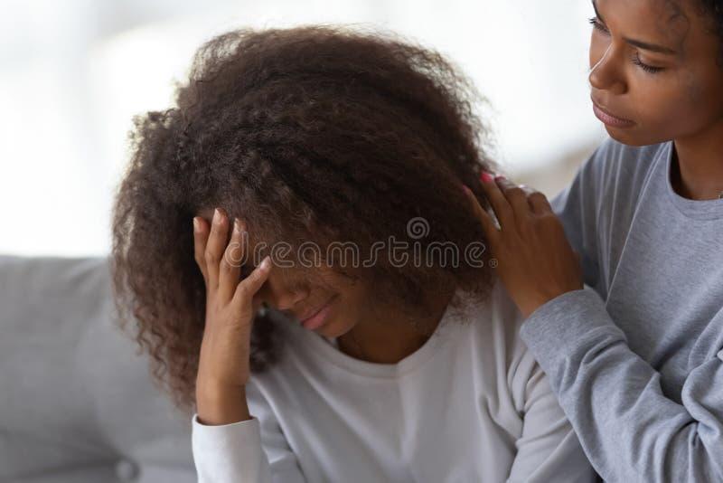 Afrikaanse Amerikaanse mammaomhelzing die droevige tienerdochter troosten stock afbeelding