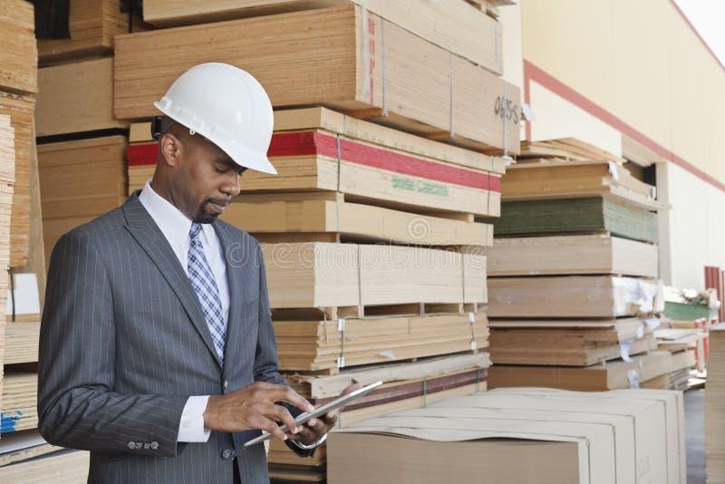 Afrikaanse Amerikaanse mannelijke contractant die tabletpc met gestapelde houten planken op achtergrond met behulp van stock foto's