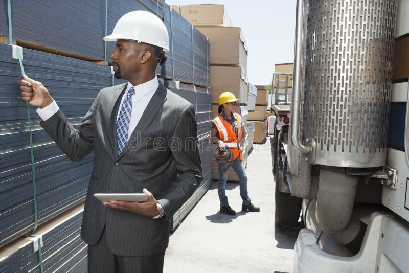 Afrikaanse Amerikaanse mannelijke ingenieur het inspecteren planken terwijl vrouwelijke werknemer die zich door flatbed vrachtwage royalty-vrije stock afbeeldingen