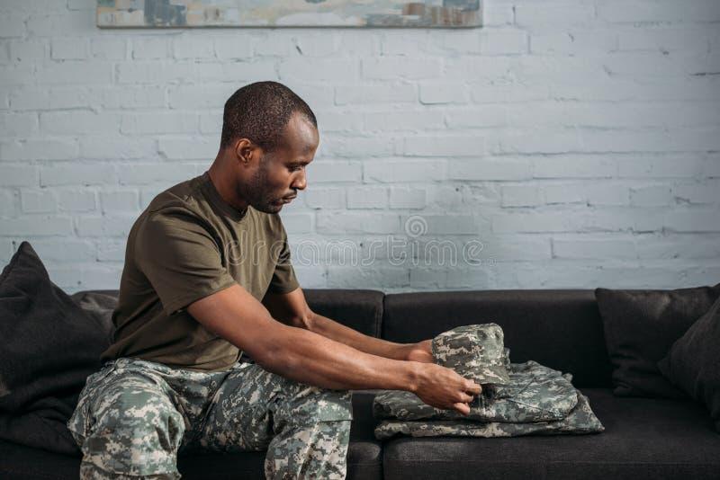 Afrikaanse Amerikaanse mannelijke militair die camouflagekleren vouwen stock foto's