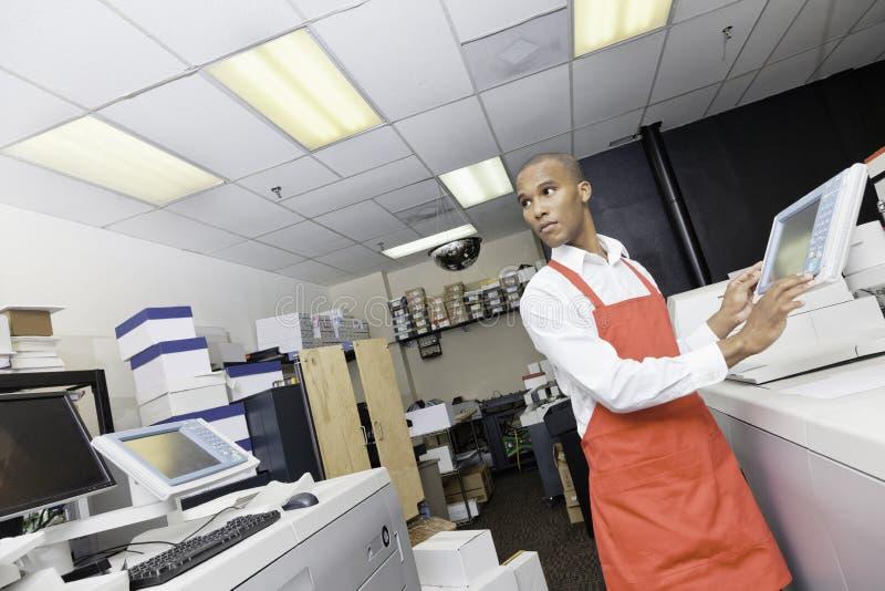 Afrikaanse Amerikaanse mens die bij drukpers werken stock fotografie