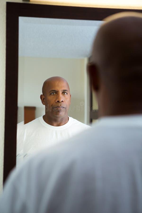 Afrikaanse Amerikaanse mens die in de spiegel kijken stock afbeelding