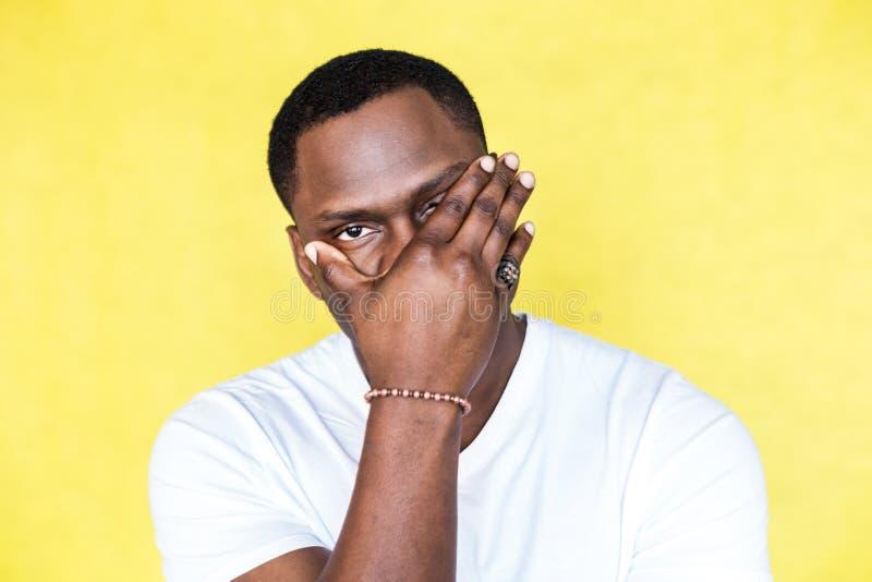 Afrikaanse Amerikaanse mens die gezicht behandelen met hand en camera bekijken stock fotografie