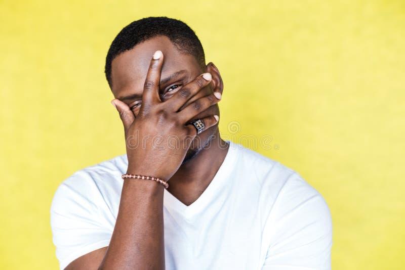 Afrikaanse Amerikaanse mens die gezicht behandelen met hand en camera bekijken royalty-vrije stock afbeeldingen