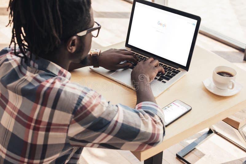 Afrikaanse Amerikaanse mens die laptop met googlewebsite en smartphone met behulp van royalty-vrije stock foto's