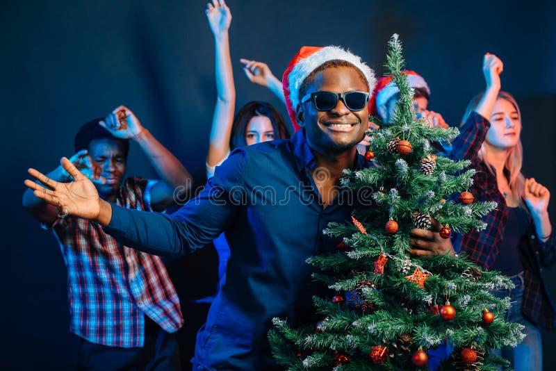 Afrikaanse Amerikaanse mens die met cristmasboom koesteren stock afbeeldingen