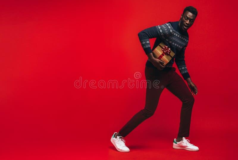 Afrikaanse Amerikaanse mens die met een gift loopt stock afbeelding