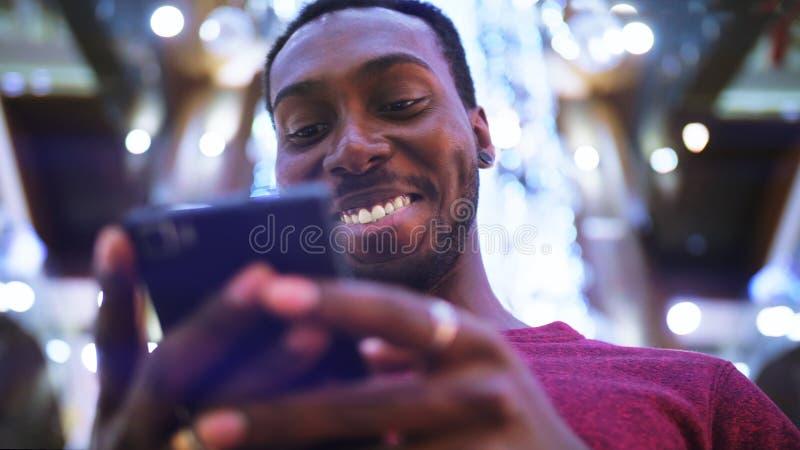 Afrikaanse Amerikaanse Mens die zaken app op slimme telefoon gebruiken stock afbeeldingen