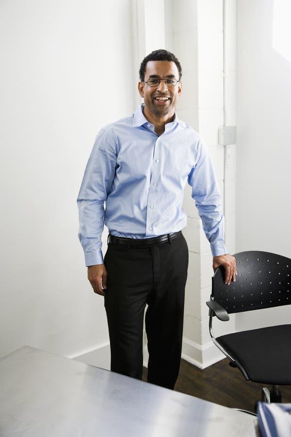 Afrikaanse Amerikaanse mens die zich in bureau bevindt royalty-vrije stock afbeeldingen