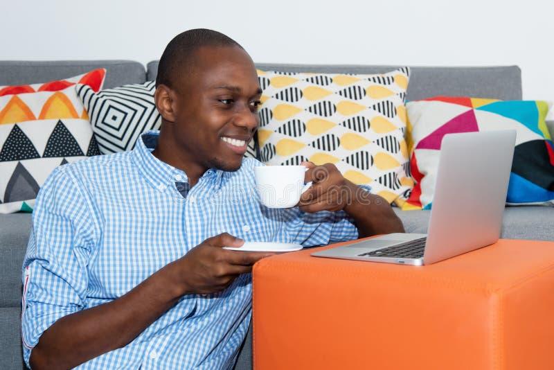 Afrikaanse Amerikaanse mens het letten op filmklem online met laptop stock fotografie