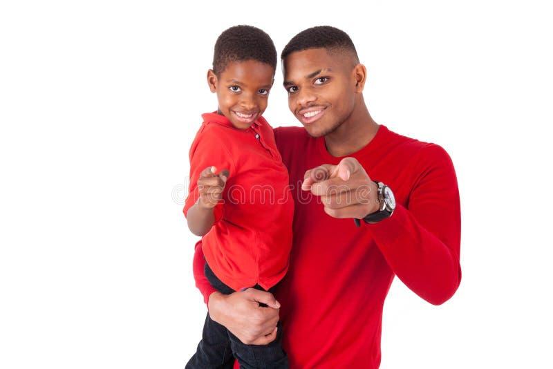 Afrikaanse Amerikaanse mens met het houden van zijn kleine die jongen op wh wordt geïsoleerd stock afbeeldingen