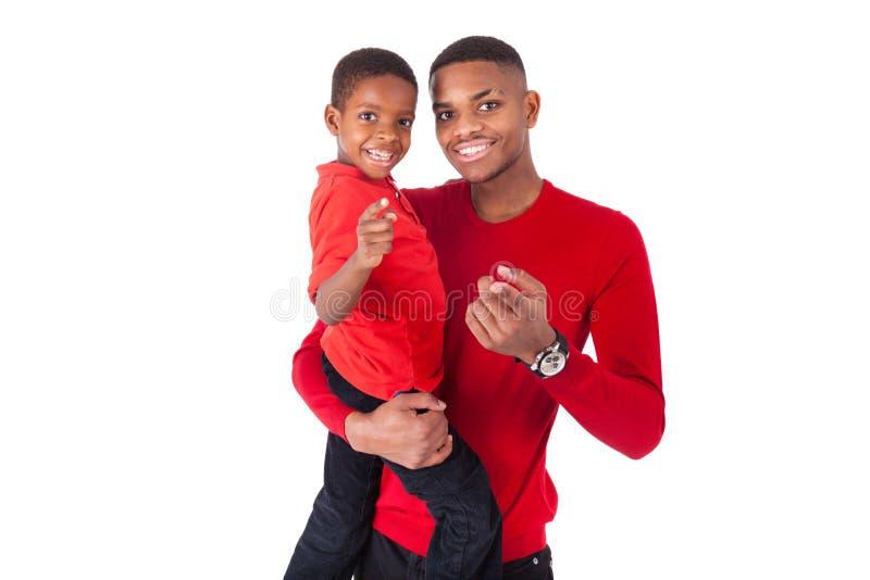 Afrikaanse Amerikaanse mens met het houden van zijn kleine die jongen op wh wordt geïsoleerd royalty-vrije stock fotografie