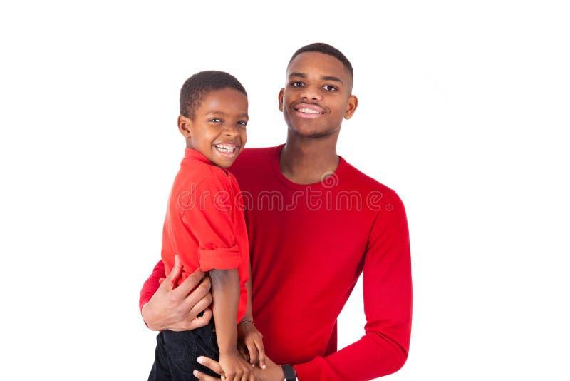 Afrikaanse Amerikaanse mens met het houden van zijn kleine die jongen op wh wordt geïsoleerd stock foto's