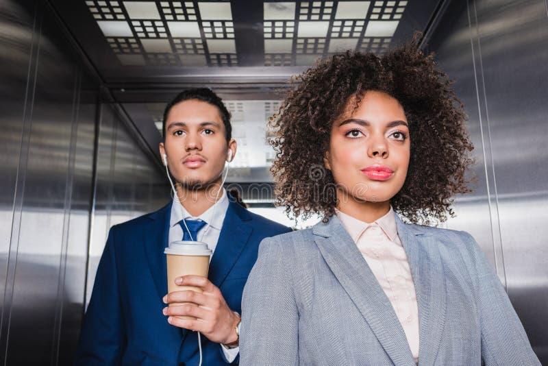 Afrikaanse Amerikaanse mens in oortelefoons met koffiekop die zich in lift bevinden stock foto's