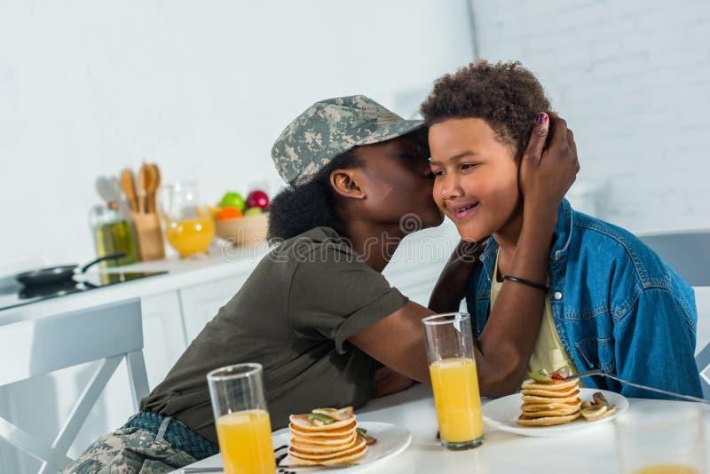 Afrikaanse Amerikaanse militair met zoon die van maaltijd genieten royalty-vrije stock afbeeldingen