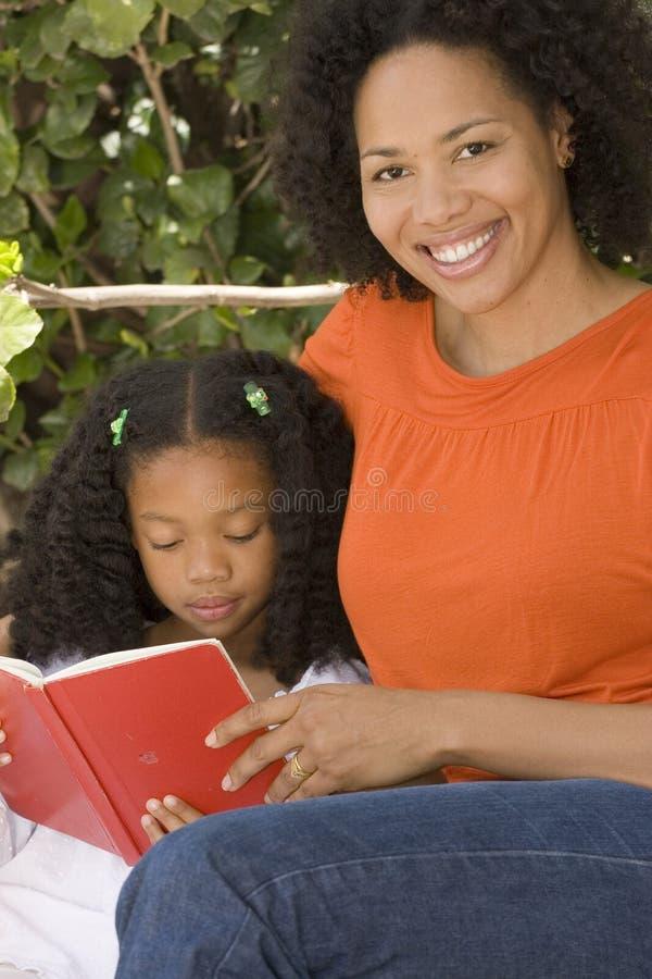 Afrikaanse Amerikaanse moeder en haar daugherlezing stock afbeeldingen