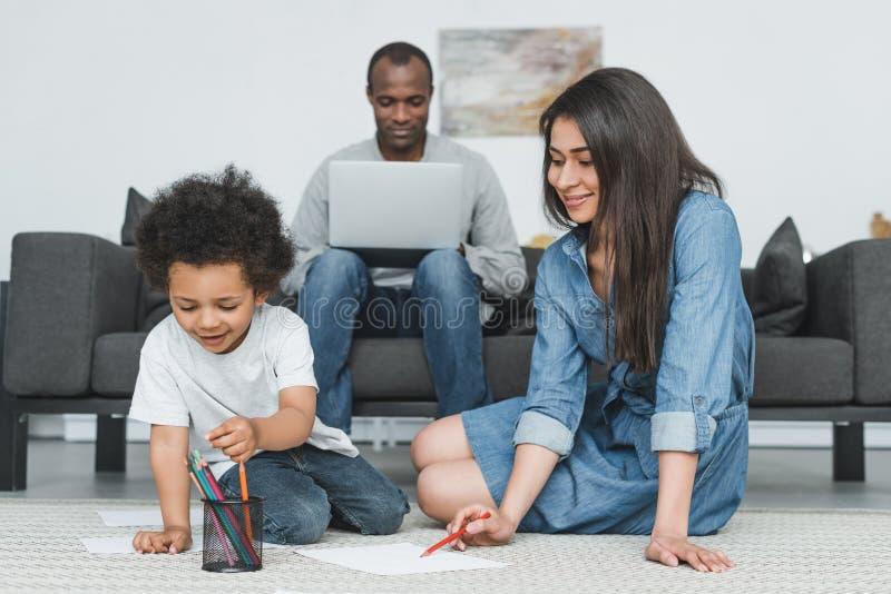 Afrikaanse Amerikaanse moeder en zoon die bij vloer thuis vader het werken trekken royalty-vrije stock afbeelding