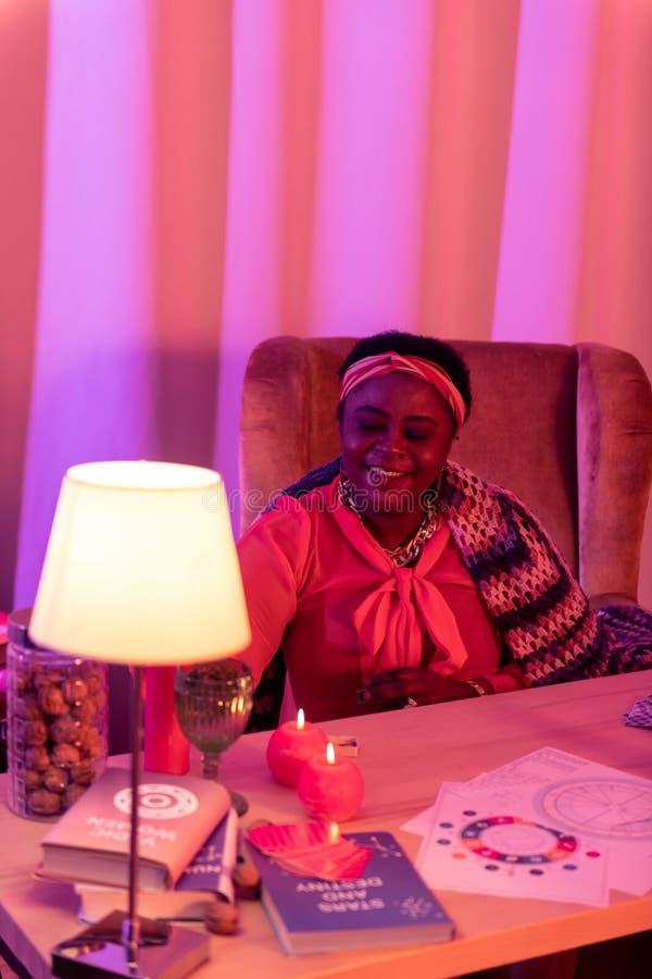 Afrikaanse Amerikaanse mollige waarzegger die in etnische versieringen bij de lijst zitten royalty-vrije stock foto's