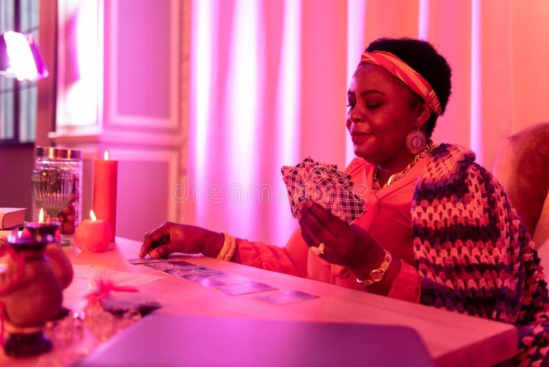 Afrikaanse Amerikaanse mollige waarzegger die in etnische versieringen de kaarten op de lijst bekijken royalty-vrije stock foto