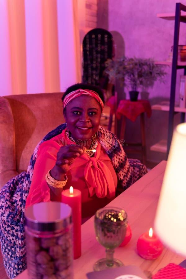 Afrikaanse Amerikaanse mollige waarzegger die in etnische versieringen een brandende gelijke houden stock fotografie