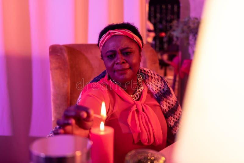 Afrikaanse Amerikaanse mollige waarzegger die in etnische versieringen ernstig kijken royalty-vrije stock foto