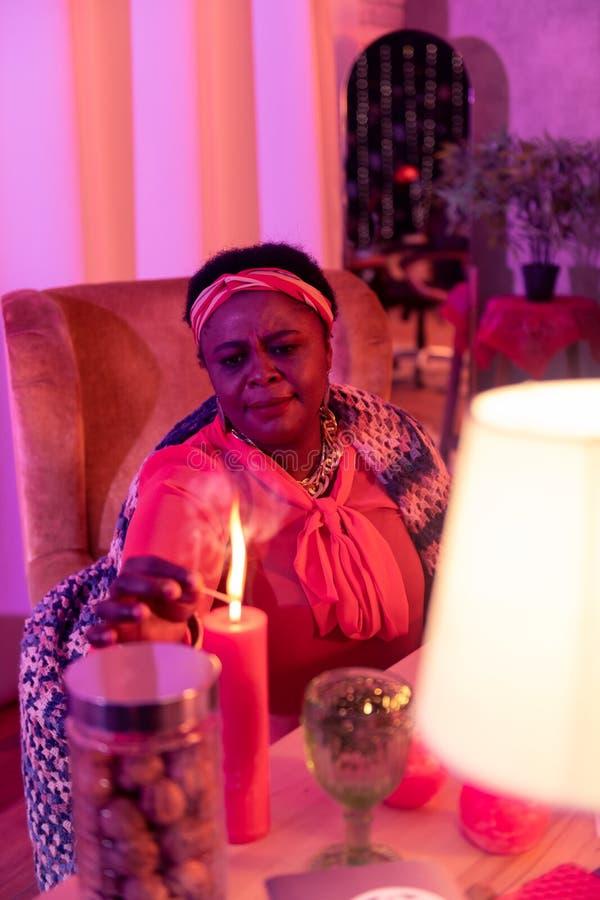 Afrikaanse Amerikaanse mollige waarzegger die in etnische versieringen geconcentreerd kijken royalty-vrije stock foto