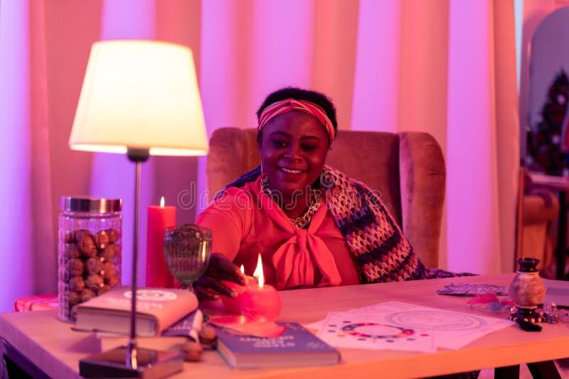 Afrikaanse Amerikaanse mollige waarzegger die in etnische versieringen goed voelen royalty-vrije stock afbeelding