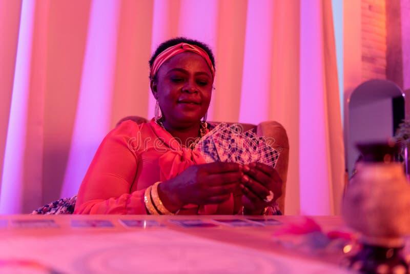 Afrikaanse Amerikaanse mollige waarzegger die in etnische versieringen interessant kijkt stock fotografie