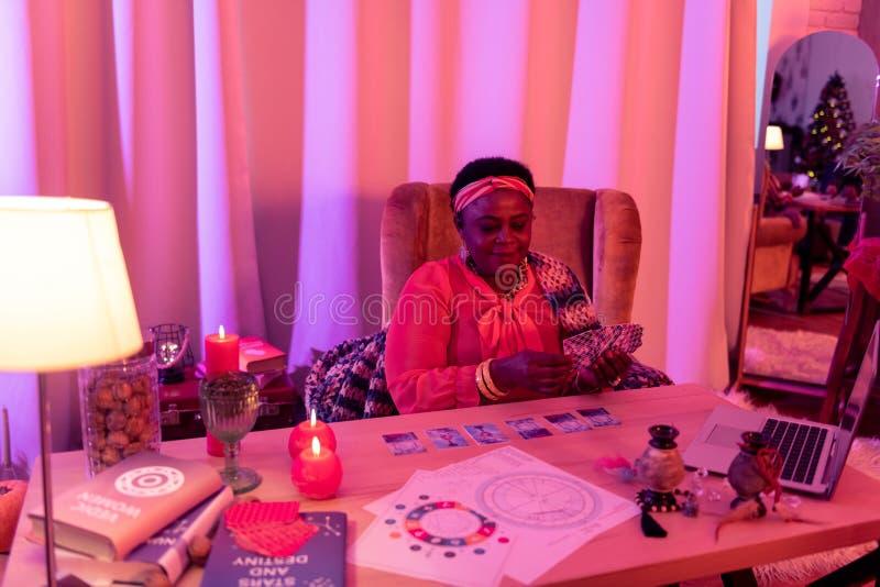 Afrikaanse Amerikaanse mollige waarzegger die in etnische versieringen kaartentarot lezen royalty-vrije stock foto