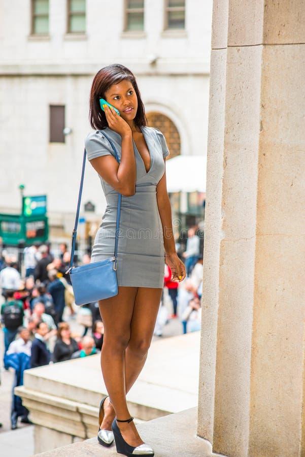 Afrikaanse Amerikaanse Onderneemster die op telefoon, het reizen, het werk spreken stock foto's