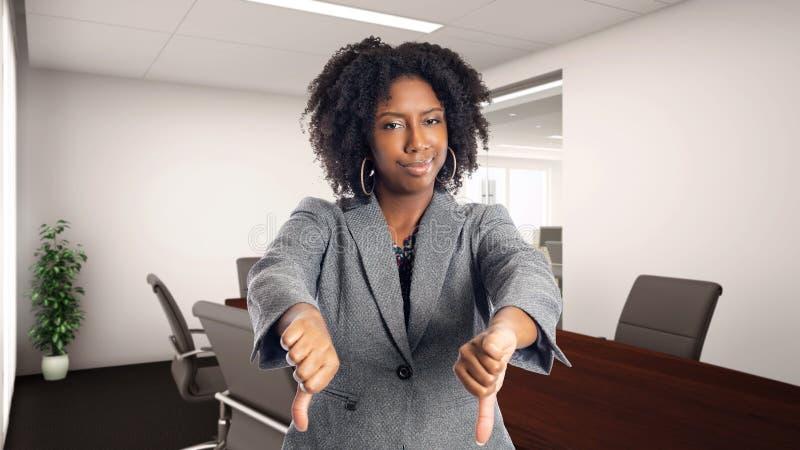 Afrikaanse Amerikaanse Onderneemster In een Bureau met neer Duimen royalty-vrije stock foto