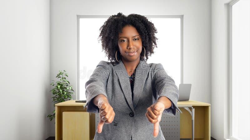 Afrikaanse Amerikaanse Onderneemster In een Bureau met neer Duimen stock foto
