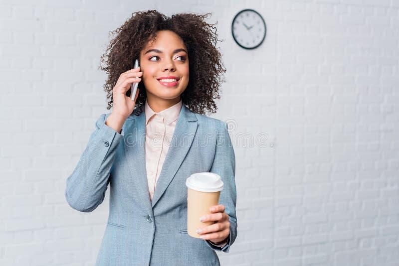 Afrikaanse Amerikaanse onderneemster met koffiekop het spreken royalty-vrije stock afbeelding