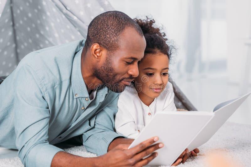 Afrikaanse Amerikaanse op vloer liggen en vader en dochter die samen lezen stock fotografie