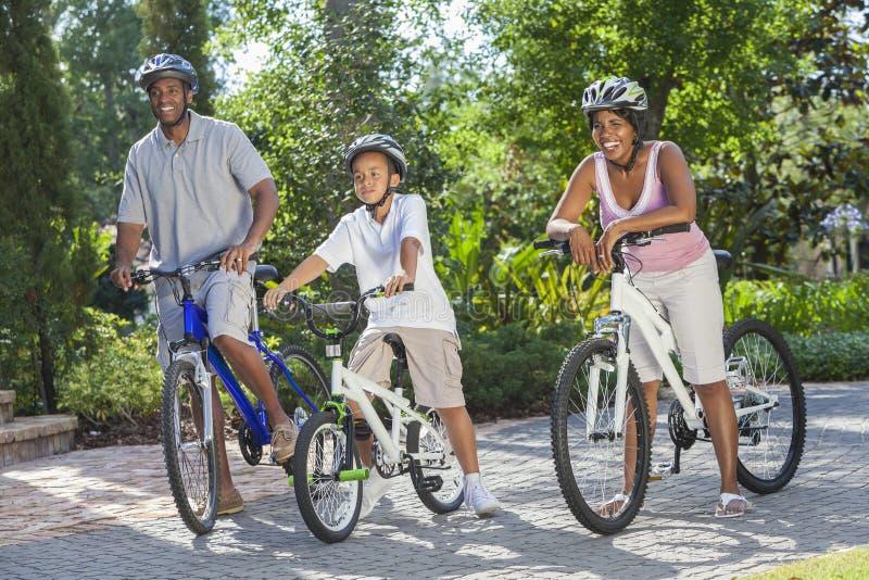 Afrikaanse Amerikaanse Ouders met de Berijdende Fiets van de Zoon van de Jongen royalty-vrije stock foto's