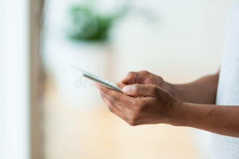 Afrikaanse Amerikaanse persoon die een tastbare mobiele smartphone houdt - Bl stock afbeelding