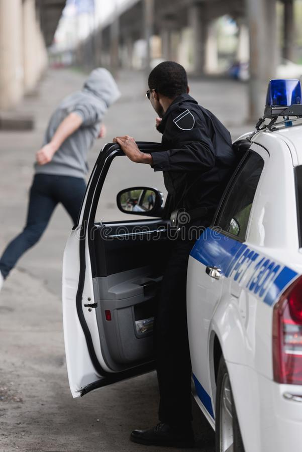 Afrikaanse Amerikaanse politieagent die van auto weggaan royalty-vrije stock afbeelding