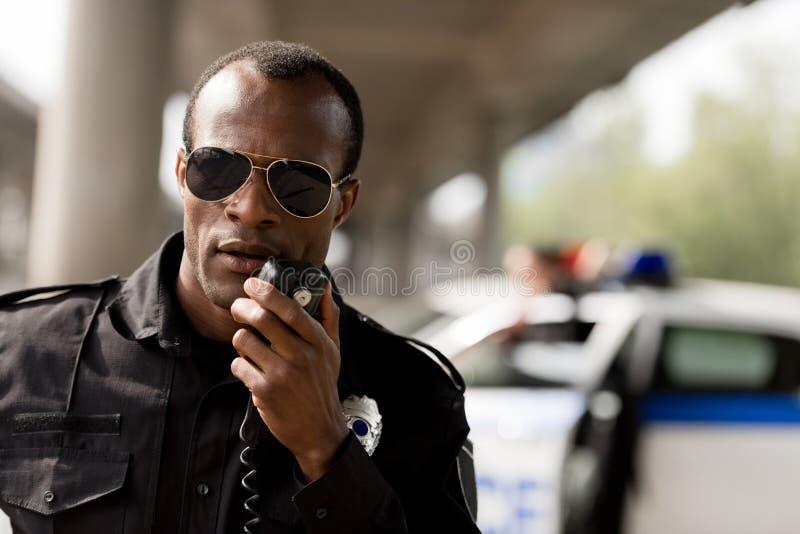 Afrikaanse Amerikaanse politieman die door walkie-talkie spreken stock foto's