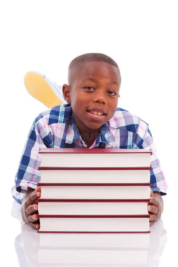 Afrikaanse Amerikaanse schooljongen met stapel een boek - Zwarte mensen stock afbeelding