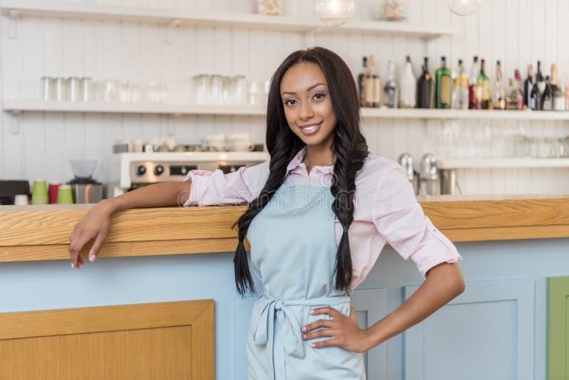 Afrikaanse Amerikaanse serveerster die en camera glimlachen bekijken terwijl status bij koffie royalty-vrije stock fotografie