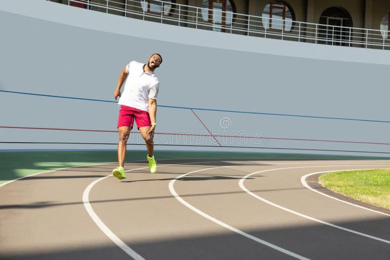Afrikaanse Amerikaanse sportieve jonge mens die aan plotselinge kniepijn lijden stock afbeeldingen