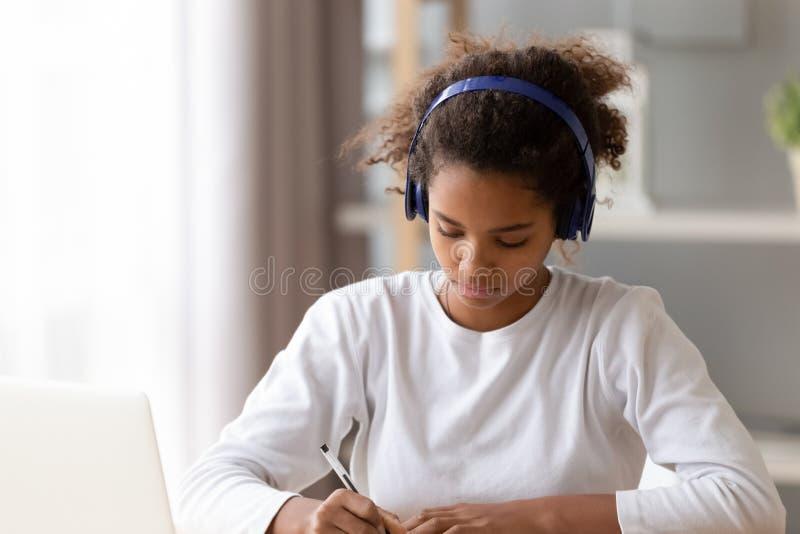 Afrikaanse Amerikaanse tiener die hoofdtelefoons draagt, die thuiswerk doen stock afbeelding