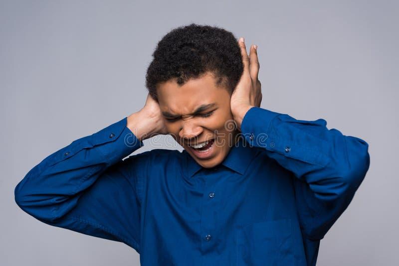 Afrikaanse Amerikaanse tienerschreeuwen in woede, die oren behandelen stock afbeelding