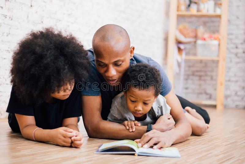Afrikaanse Amerikaanse vader die een verhaal van de sprookjemythe voor jonge geitjes thuis lezen royalty-vrije stock fotografie