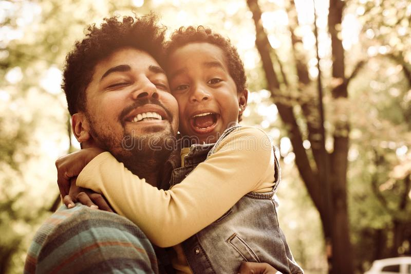 Afrikaanse Amerikaanse vader die weinig dochter in park koesteren stock foto's