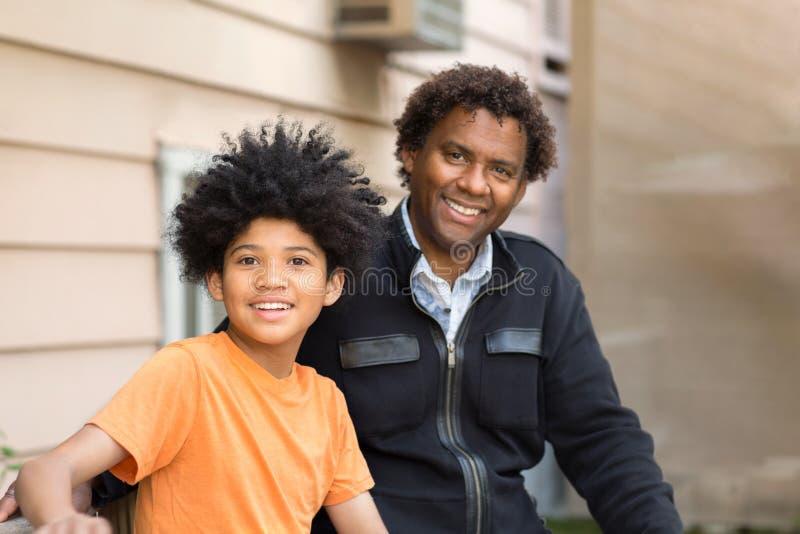 Afrikaanse Amerikaanse vader omhelsde zijn zoon en glimlachte royalty-vrije stock afbeeldingen