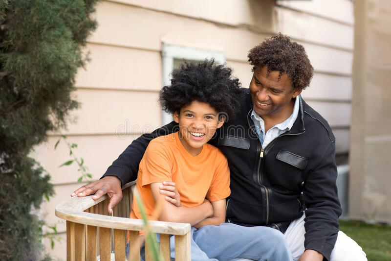 Afrikaanse Amerikaanse vader omhelsde zijn zoon en glimlachte royalty-vrije stock fotografie