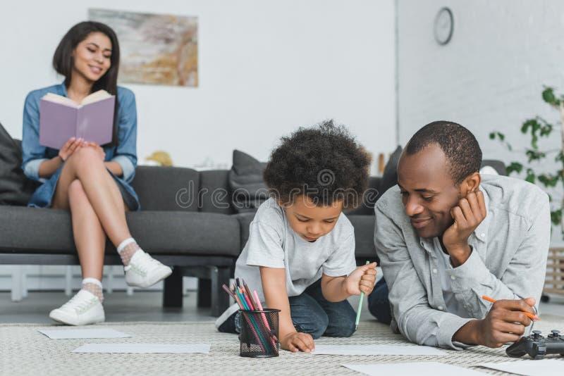 Afrikaanse Amerikaanse vadertekening met zoon en moederlezingsboek royalty-vrije stock foto