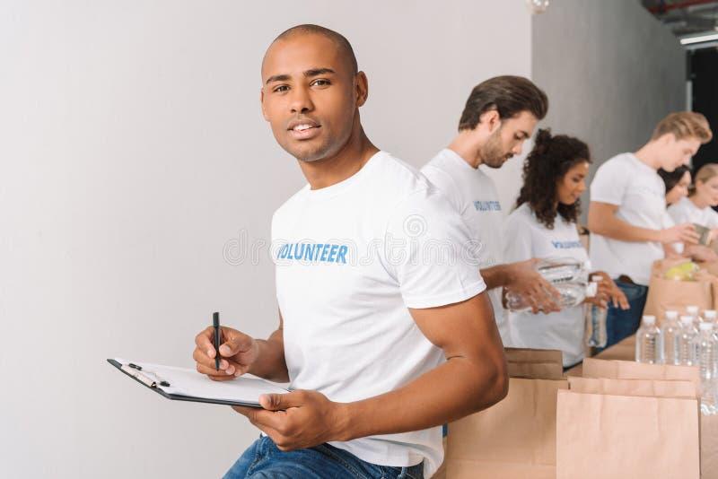 Afrikaanse Amerikaanse vrijwilliger met klembord stock afbeelding